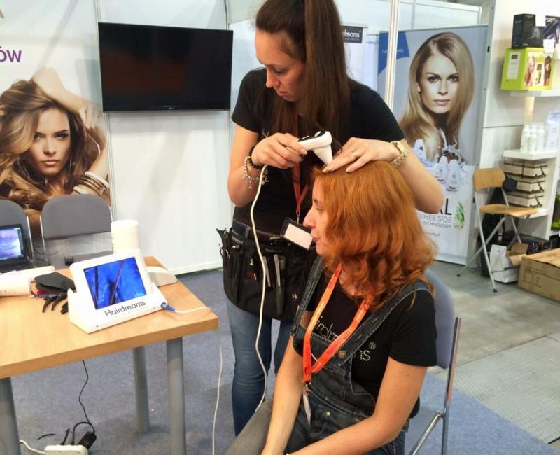 Fryzjerka przy pomocy kamery sprawdza skórę głowy klientki